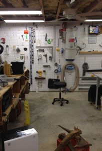 """A high-capacity dehumidifier (lower left) combined with a ceiling fan (upper right) for circulation, centrally-placed among cast-iron power tools minimizes rust risk.  As an added bonus, the brisk flow of dry air from the dehumidifier can air-dry wood in no time.  The collection being dried in this photo consists of boscoyos, Cajun French for """"cypress knees."""""""